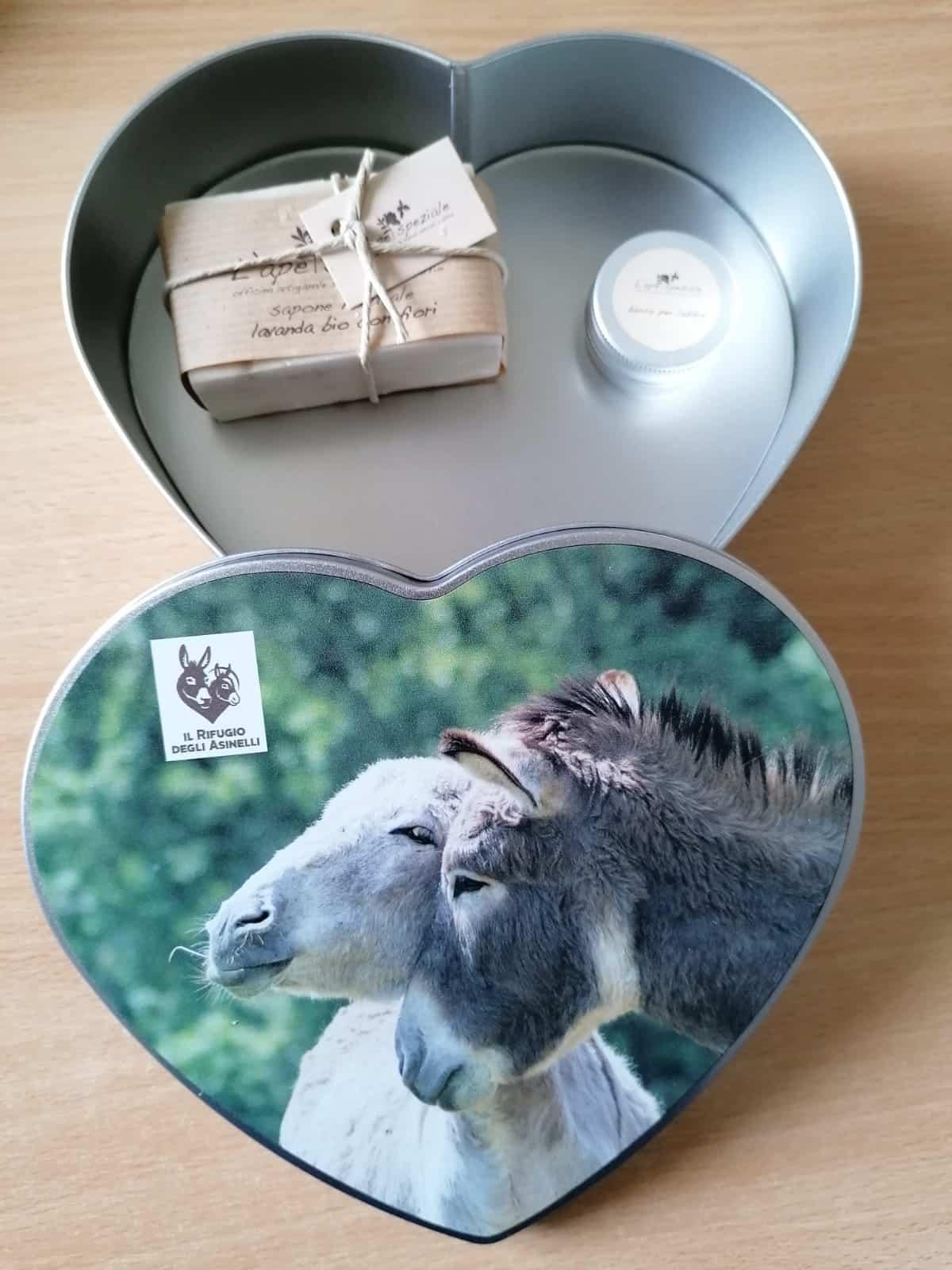 """Scatola in latta con immagine asinelli e logo """"Il Rifugio degli Asinelli"""" contenente una saponetta e un burro labbra bio de """"L'Ape Speziale"""""""