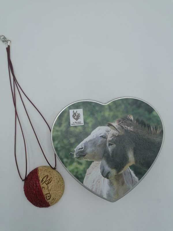 Collana asino e striature in cartapesta, realizzata artigianalmente e scatola in latta a forma di cuore con foto asinelli. Dimensioni: 18,3 x 17,0 x 4,7 cm