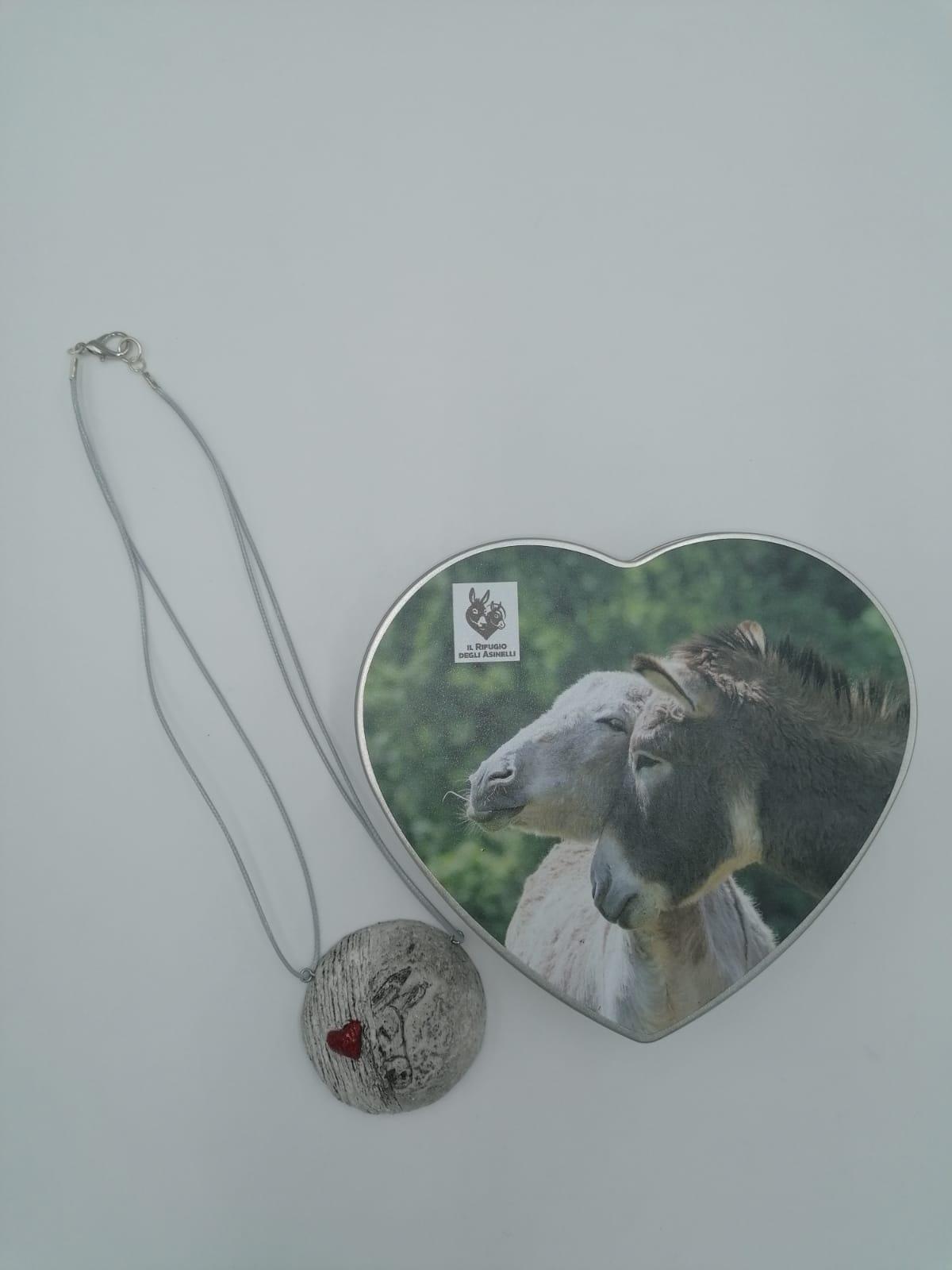Collana asino e cuore in cartapesta, realizzata artigianalmente e scatola in latta a forma di cuore con foto asinelli. Dimensioni: 18,3 x 17,0 x 4,7 cm